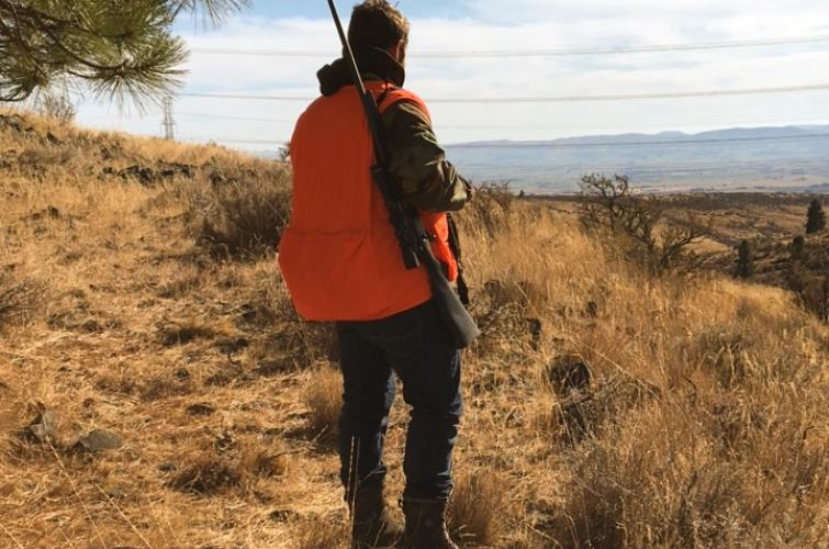 Hunter in the field wearing blaze orange