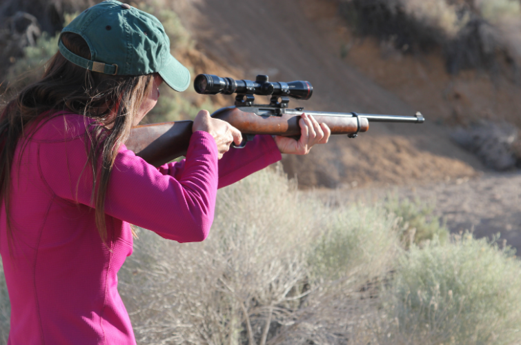 Woman aims rifle outdoors for target practice