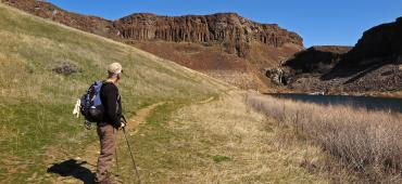 Person hikes along trail in shrubsteppe landscape