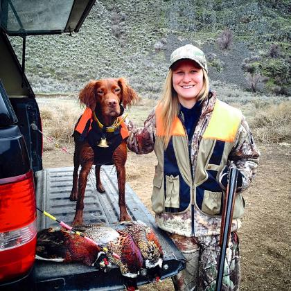 Photo of a hunter holding her shotgun and petting her dog with three harvested pheasants.