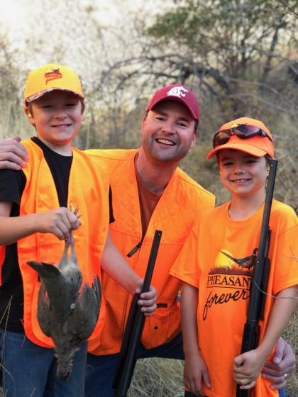 A young boy holding his first harvested partridge smiling with his father and brother. All are dressed in hunter orange.