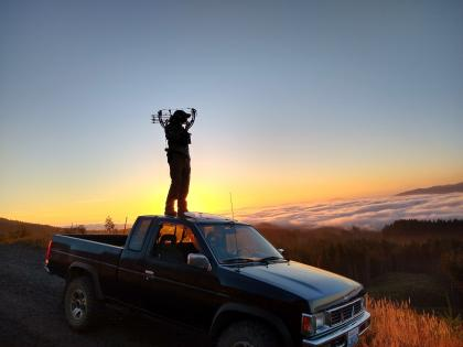 Photo of a bow hunter standing on the roof of a pickup truck lookout out over a scenic landscape at sunset.