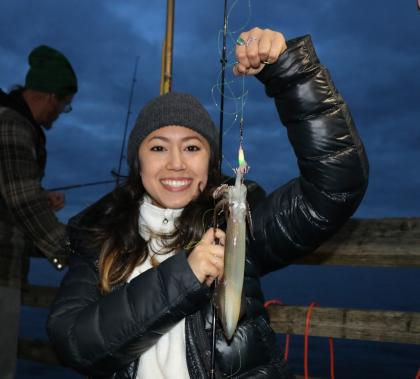 A young woman holds up a squid she caught.