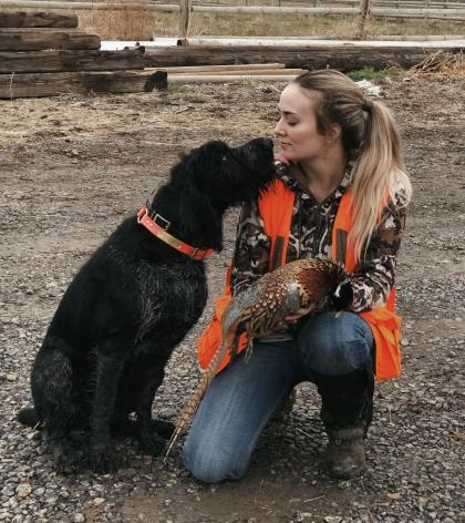 Photo of a hunter holding a harvested pheasant kneeling nose-to-nose with her dog.