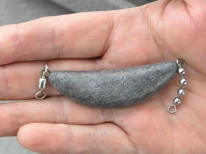 A banana or trolling sinker in the palm of a fisherman's hand