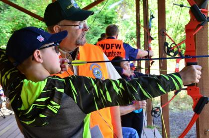 Boy prepares to shoot an arrow at a National Hunting and Fishing Day event