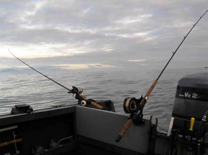 Photo of boat with two fishing poles set up one off of the back and the other off of the side of the boat