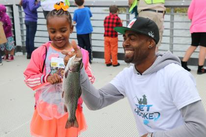 Proud father holding a freshly caught trout smiling broadly with his young daughter looking at the fish skeptically.