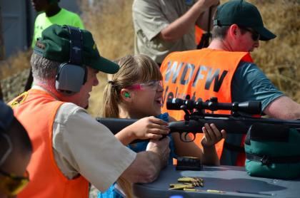 Little girl receives shooting lesson from WDFW volunteer.