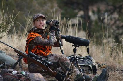 Female hunter wearing cammo and hunter orange looking through binoculars and her rifle. sitting next to a spotting scope and