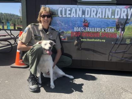 Sgt. Pam Taylor sits next to mussel-sniffing dog (Puddles) in front of clean, drain, dry sign