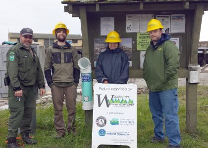 WDFW personnel and volunteers standing next to a monofilament recycling bin installed in Port Townsend, WA