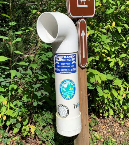 A monofilament recycling bin attached to a sign post, Deep Lake, WA