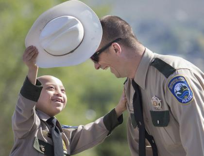 Child takes the hat off a WDFW Enforcement officer